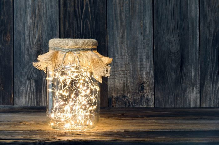 Christmas light in a glass jar against wooden boards