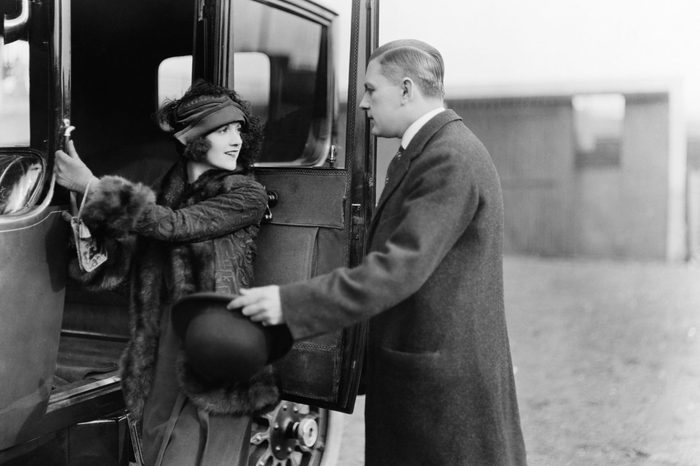 Profile of a man helping a young woman board a car