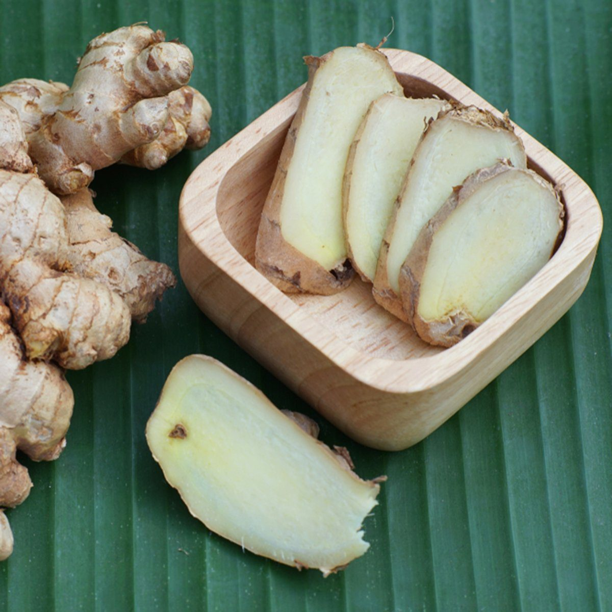 Fresh ginger root and ginger sliced on green leaf background