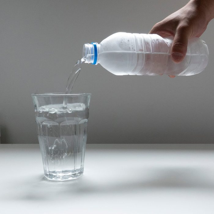 Image picture pouring plastic bottle of water into glass glass