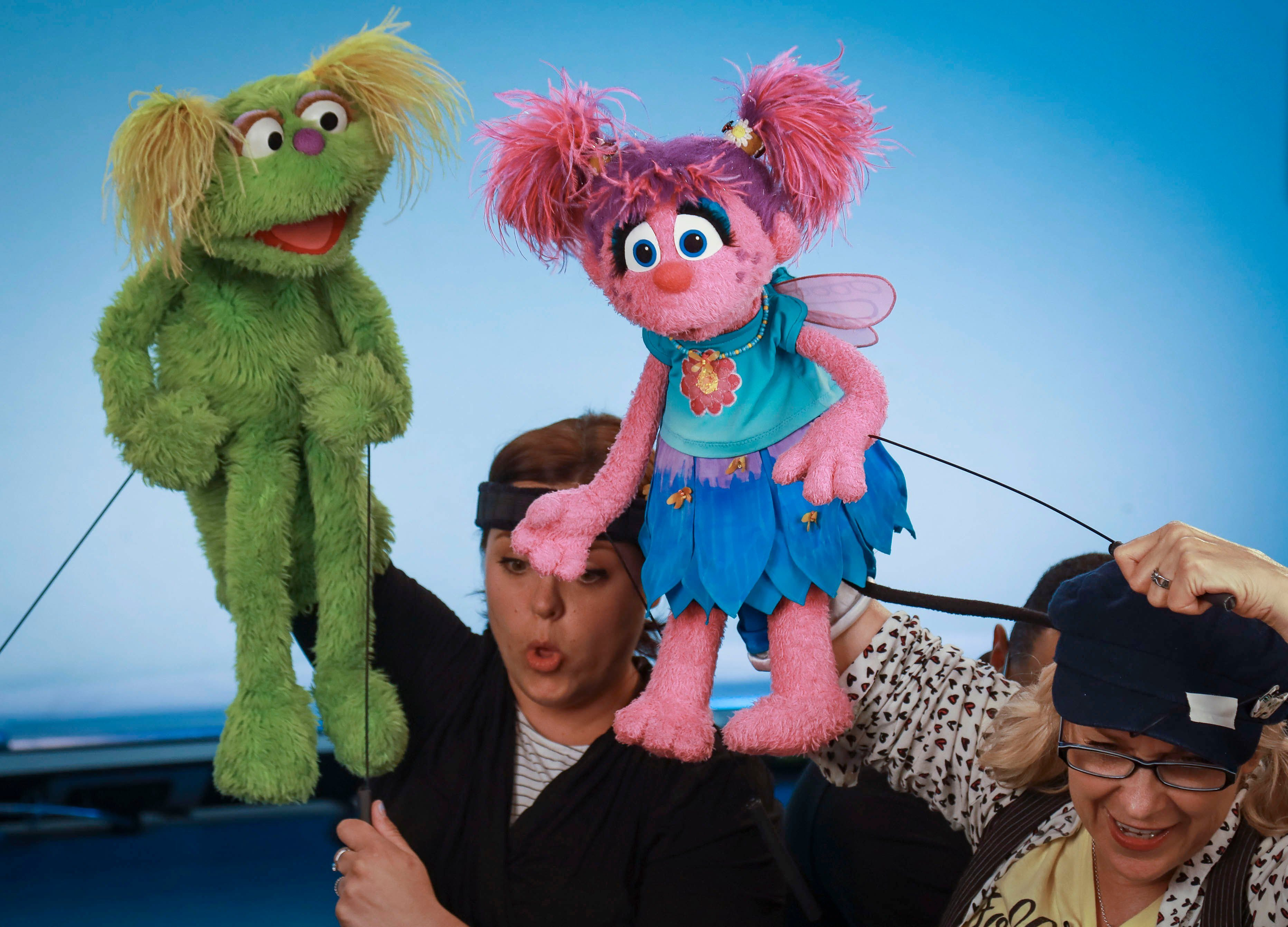 """Mandatory Credit: Photo by Bebeto Matthews/AP/Shutterstock (10440203b) This photo shows puppeteers Haley Jenkins, left, and Leslie Carrara-Rudolph performing with their """"Sesame Street"""" muppets Karli and Abby Cadabby, respectively, for segments about parental addiction in New York. Sesame Workshop is addressing the issue of addiction. Data shows 5.7 million children under 11 live in households with a parent with substance use disorder TV-Sesame Street-Addiction, New York, USA - 06 Aug 2019"""