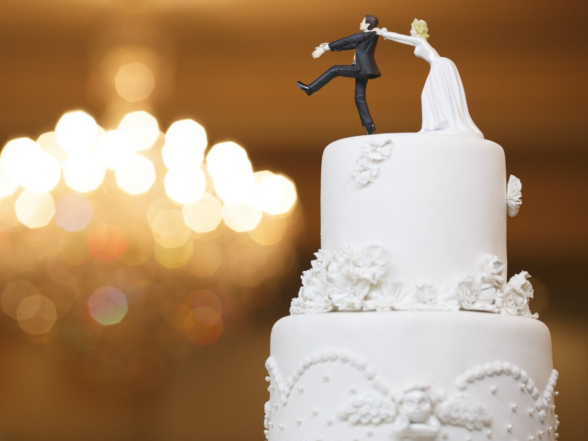 Funny bride and groom doll on wedding cake