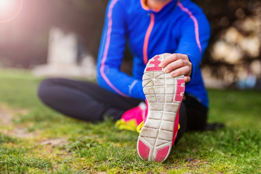 Woman in workout gear stretching her leg outdoors.