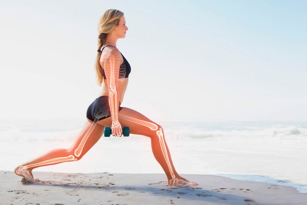 woman on the beach doing a lunge with skeletal structure outlined