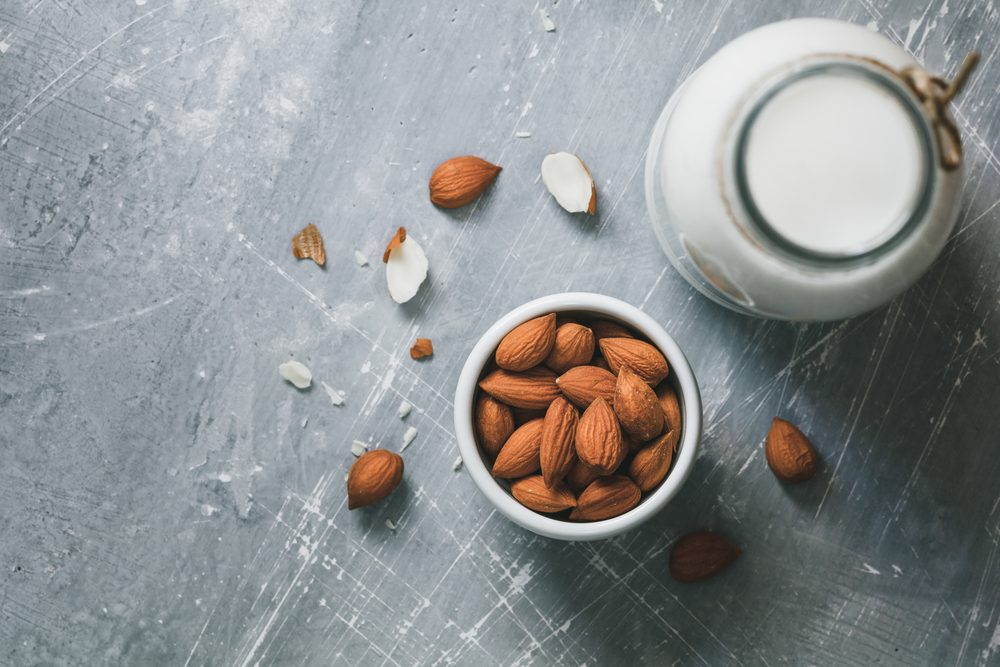 Top view of the almond milk in the glass bottle with almond nuts in the white bowl on the grey table.