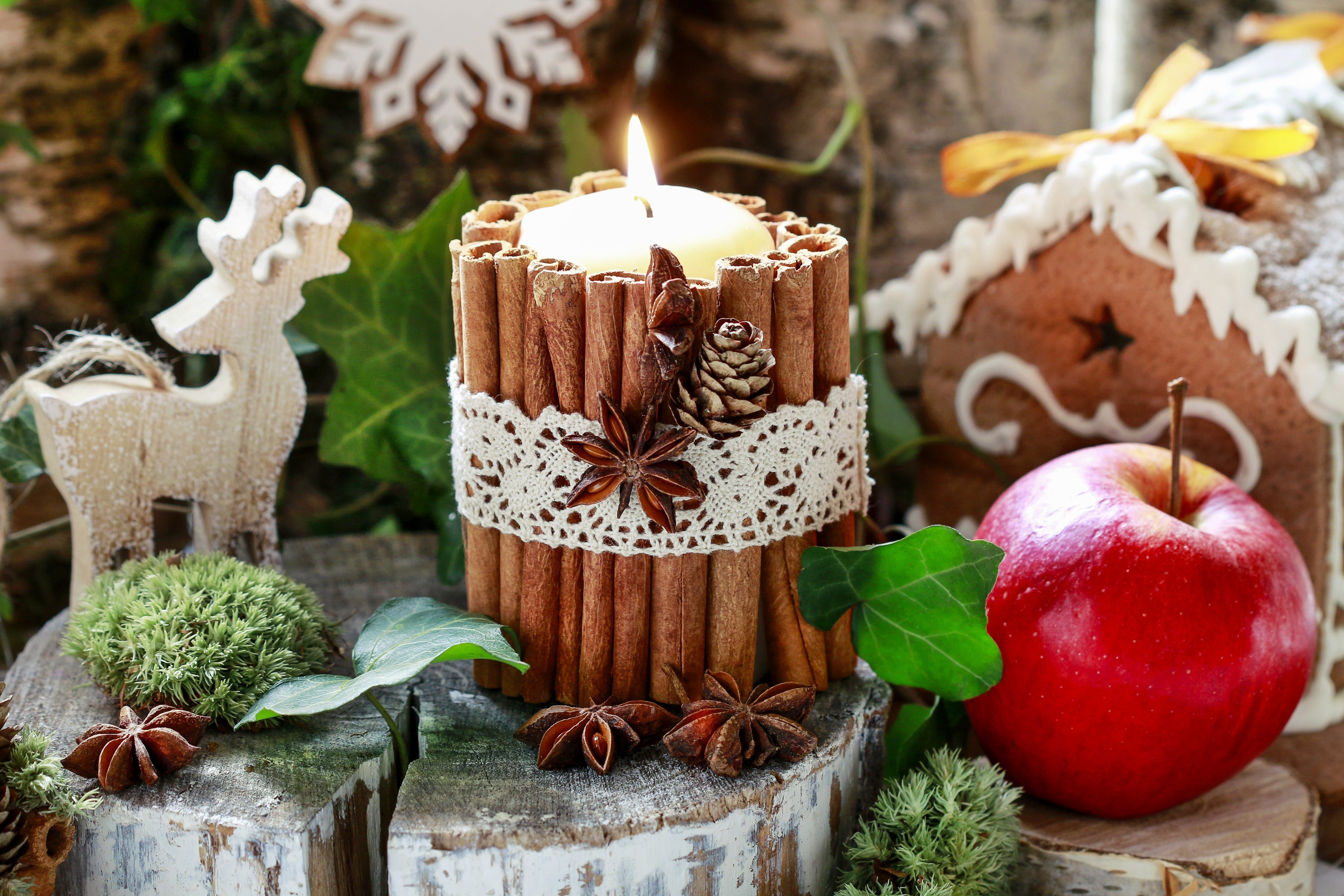 Candle decorated with cinnamon sticks, moss, ivy leaves and wooden deers - beautiful natural Christmas arrangement.