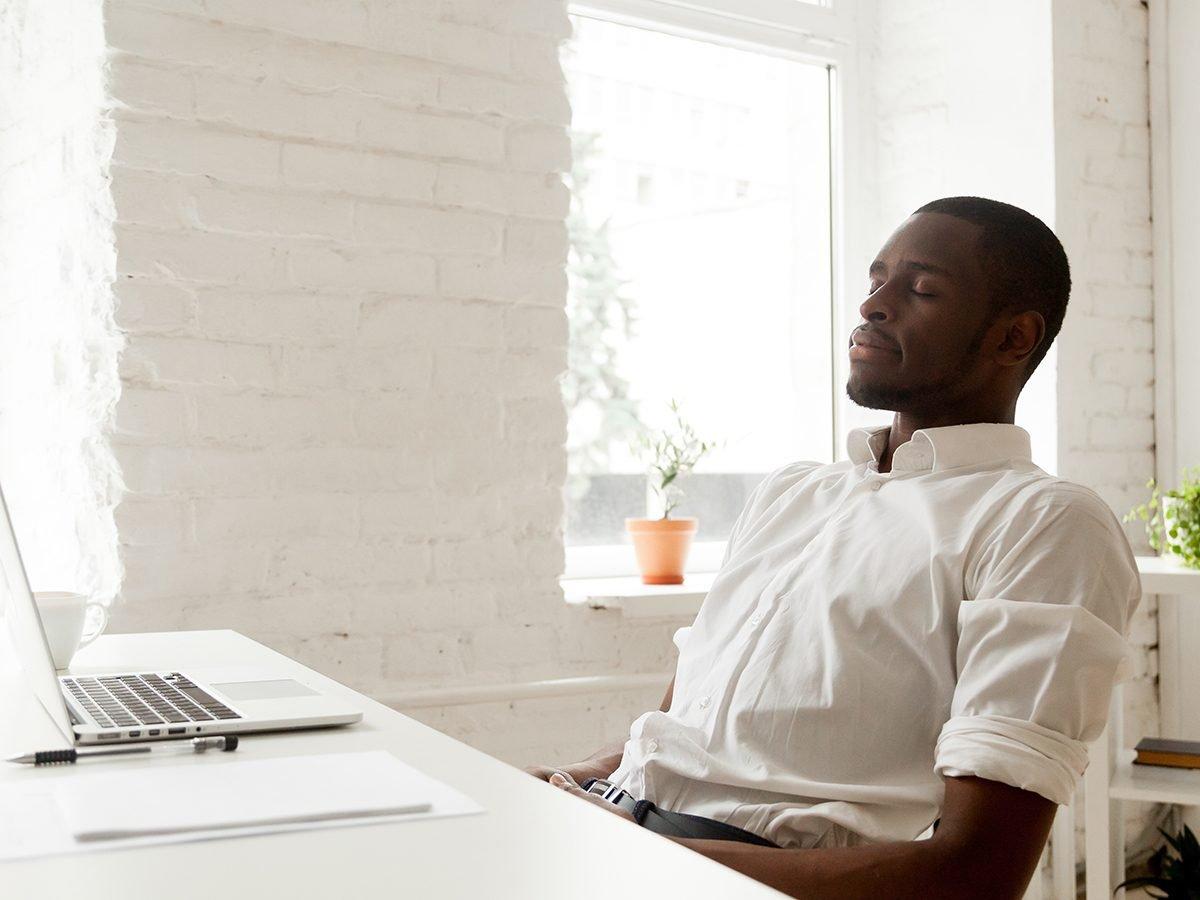 Health benefits of meditation - man calm breathing at desk