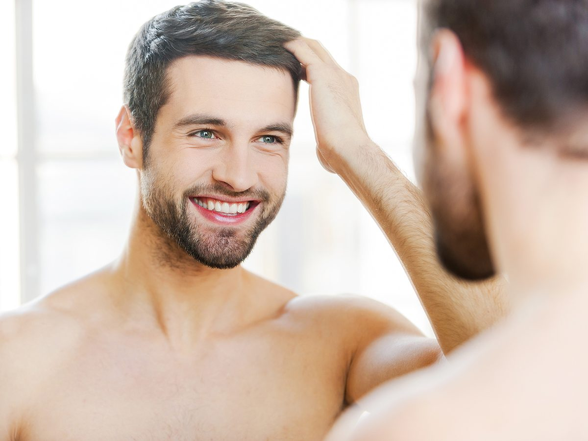Health benefits of meditation - man looking in mirror smiling