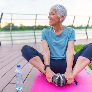 New years resolutions to help you live longer - Woman stretching outside
