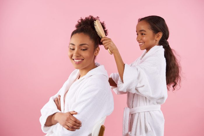 Little African American girl is combing mother hair. Isolated on pink background. Studio portrait.