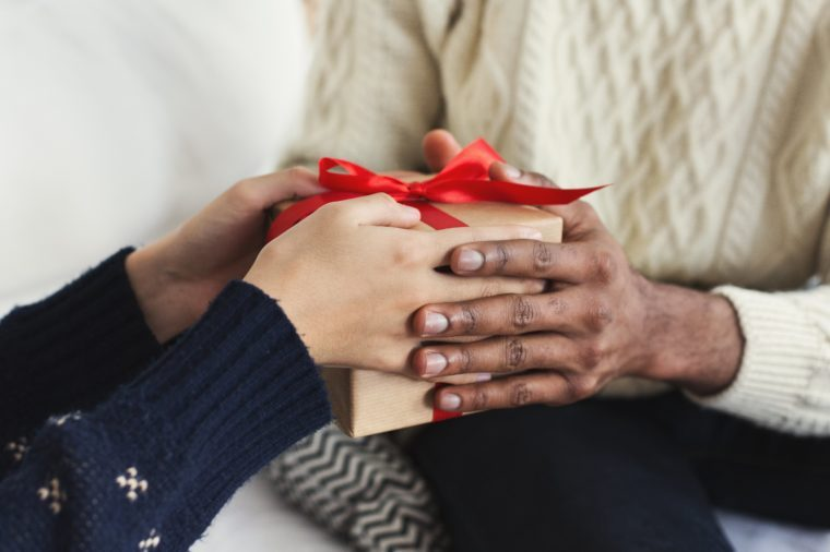 Presenting gifts as Christmas eve tradition. African-american couple exchanging xmas presents, closeup, copy space