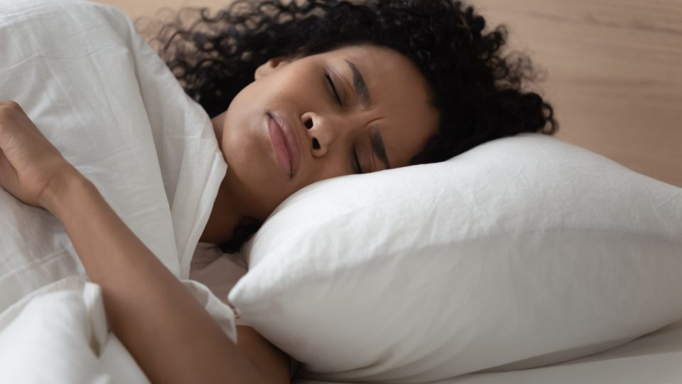 Close up african woman lying in bed has nightmares bad sleeping, uncomfortable head position on pillow poor-quality mattress, stressful lifestyle, hear alarm signal lack of energy to wake up concept