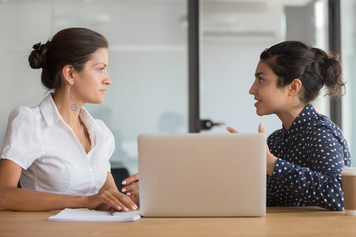 Enthusiastic young indian employee sharing new project ideas with serious female boss. Diverse business woman team discussing working moments at office. HR manager listening to interns experience