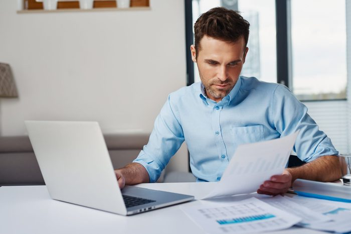 Young man working with laptop at home browsing bills and documents