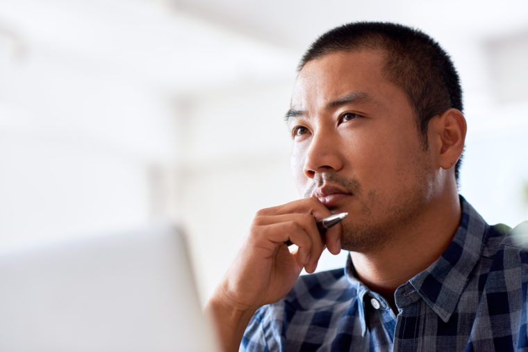 Young Asian designer deep in thought with a hand on his chin while working on a laptop alone at a desk in a modern office