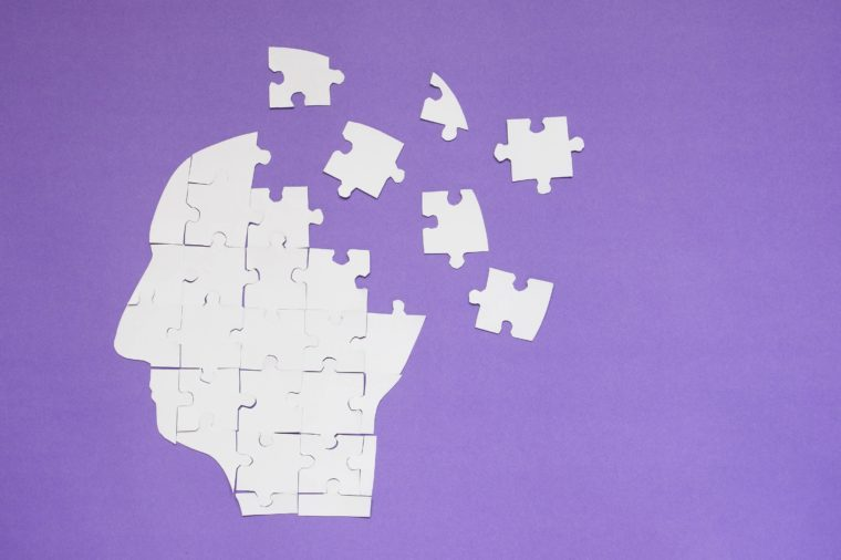 White jigsaw puzzle as a human brain on purple background w/ copy space. Creative idea for memory loss, Alzheimer's disease, dementia, Parkinson's disease, emotion stress and mental health concept.