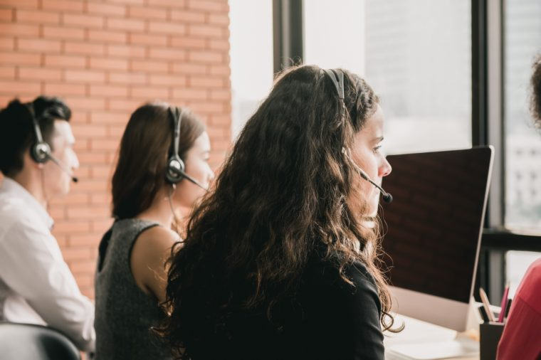 Side view of telemarketing call center staff with headsets providing business customer service facing computer monitors and office window with red brick wall background