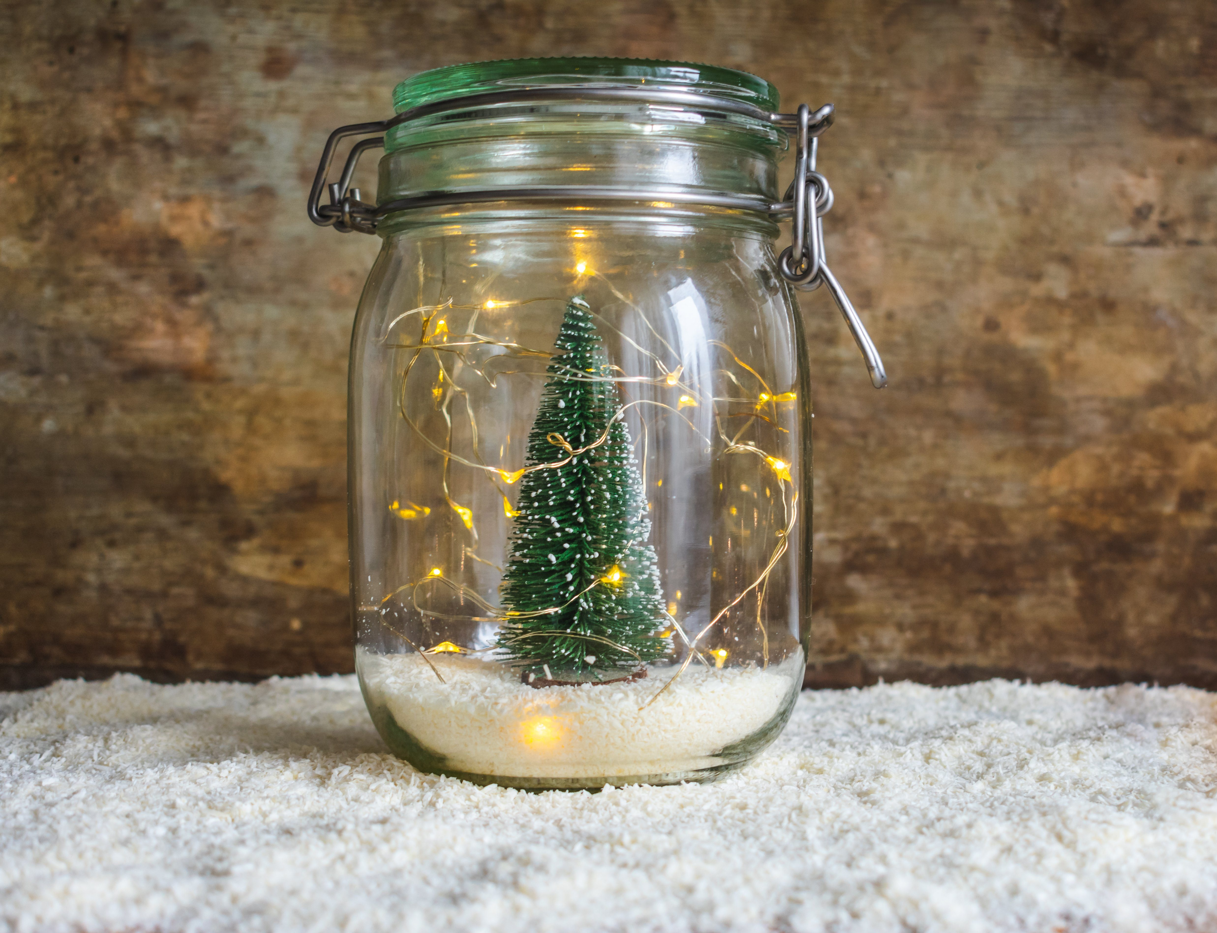 View of a jar with snow and a green Christmas tree decoration and Christmas lights on white snow and a wooden rustic background with copy space. Christmas or winter interior decoration or design