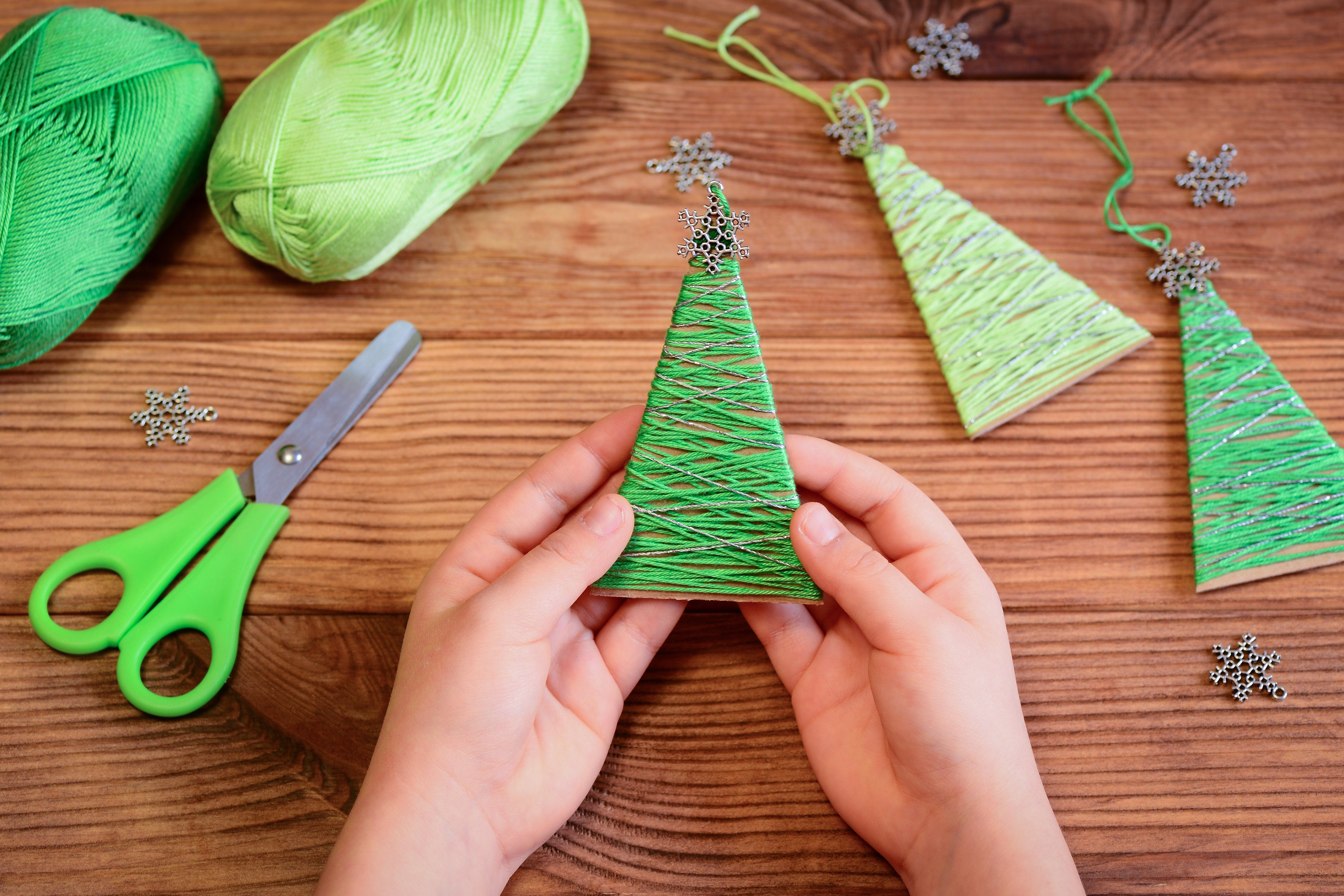 Kid is holding a Christmas tree decoration in his hands. Kid is showing a Christmas tree decoration. Merry Christmas tree project for kids. Scissors, green cotton yarn on a wooden table