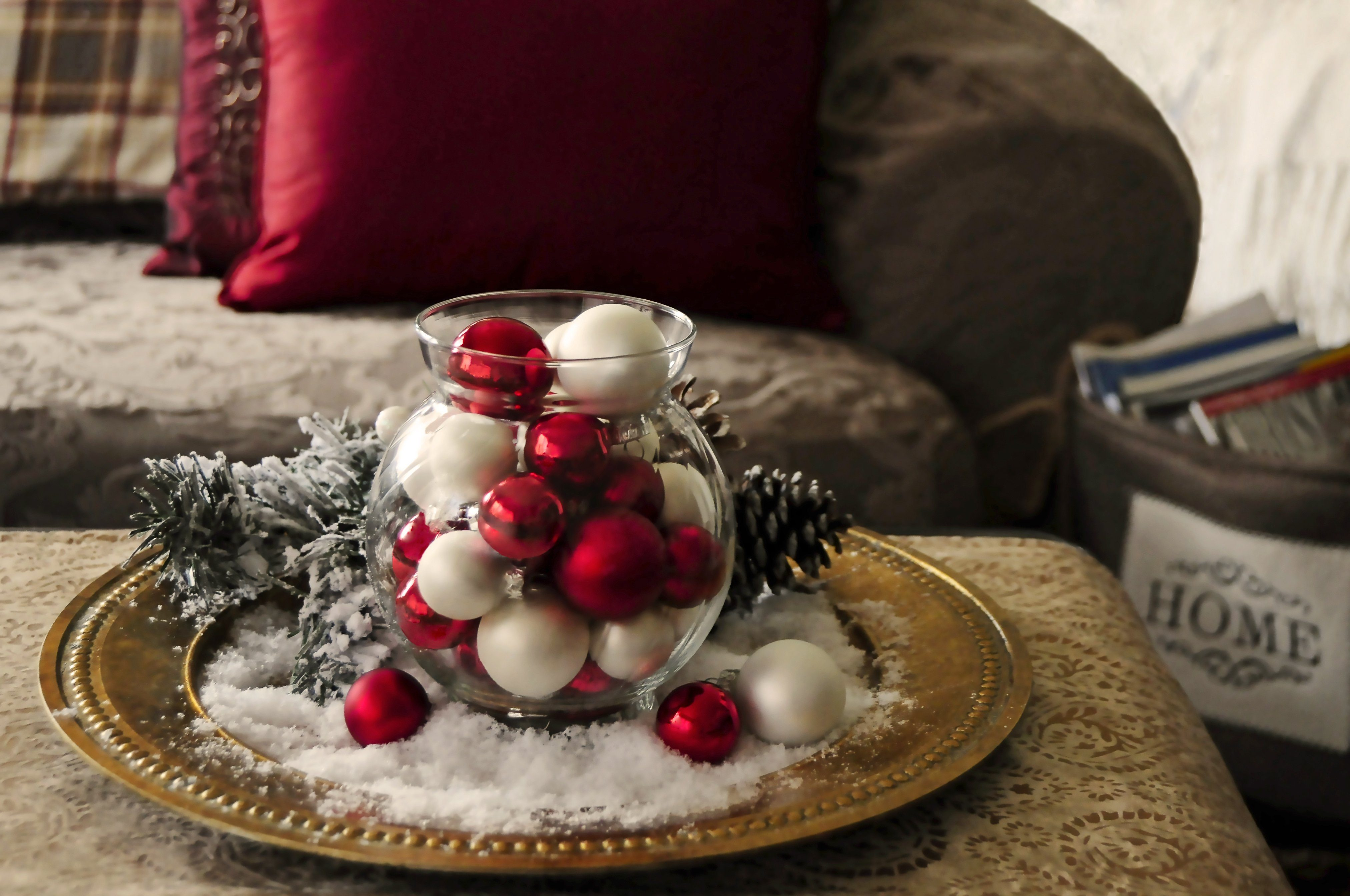 "Vintage tray with glass vase filled with red and pearl baubleswith snow and evergreen centerpiece on coffee table by chair with magazine holder saying ""home"" on the front holding christmas magazine"