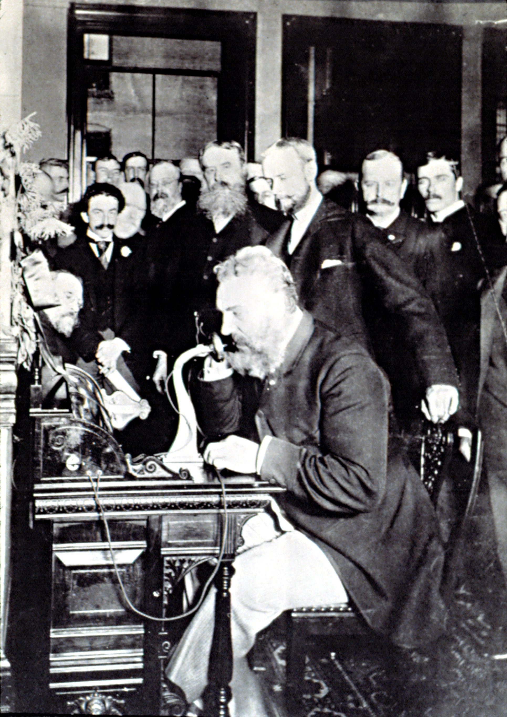 ALEXANDER GRAHAM BELL, demonstrating how to make a phone call in New York, March 12, 1876. Bell is talking to Thomas Watson & says, Mr. Watson -- Come here -- I want to see you.