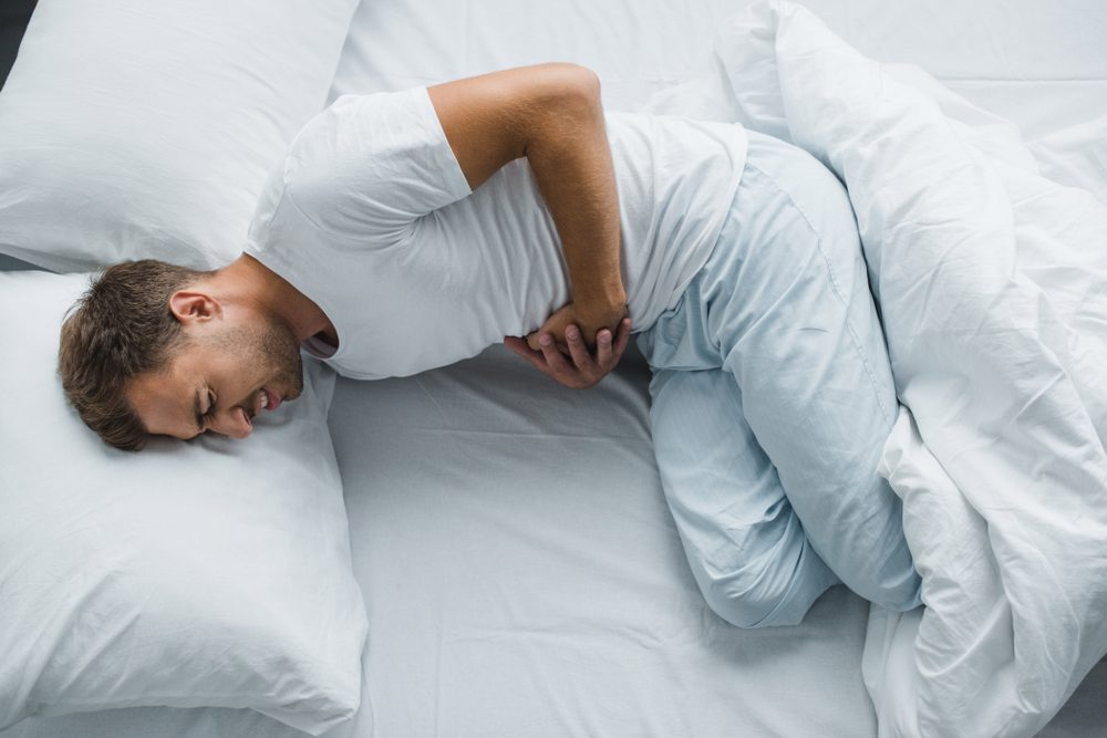 top view of man lying in bed and suffering from stomach pain