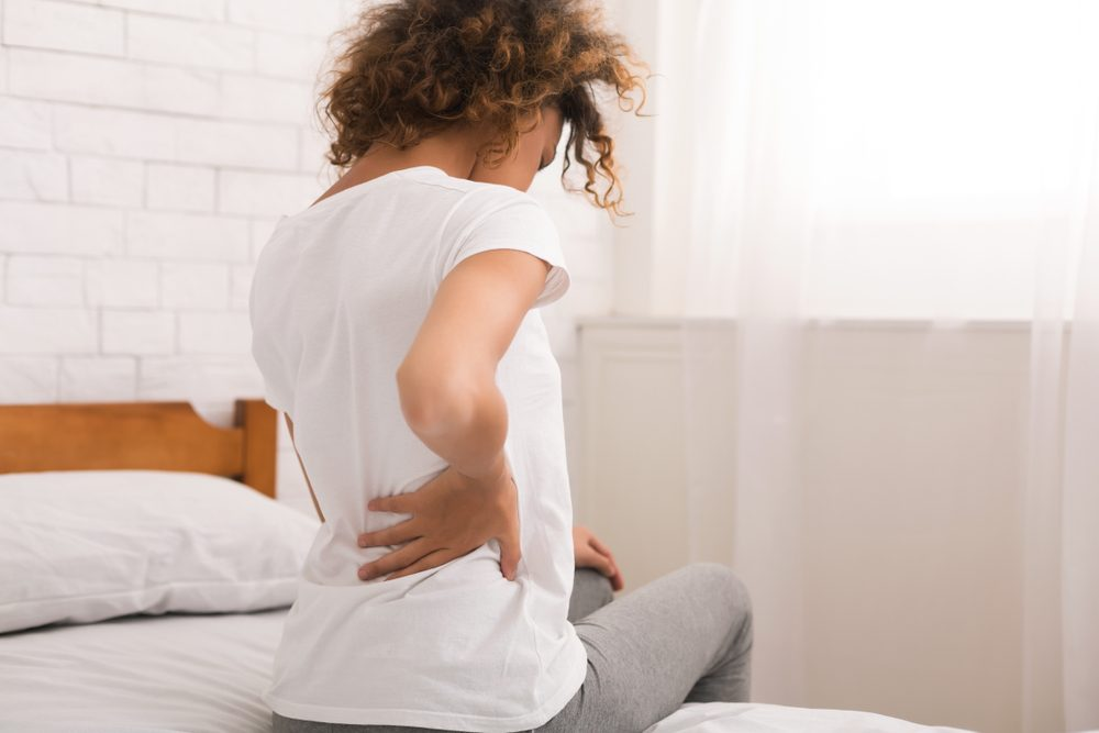 African-american woman having back pain after sleep, sitting on bed