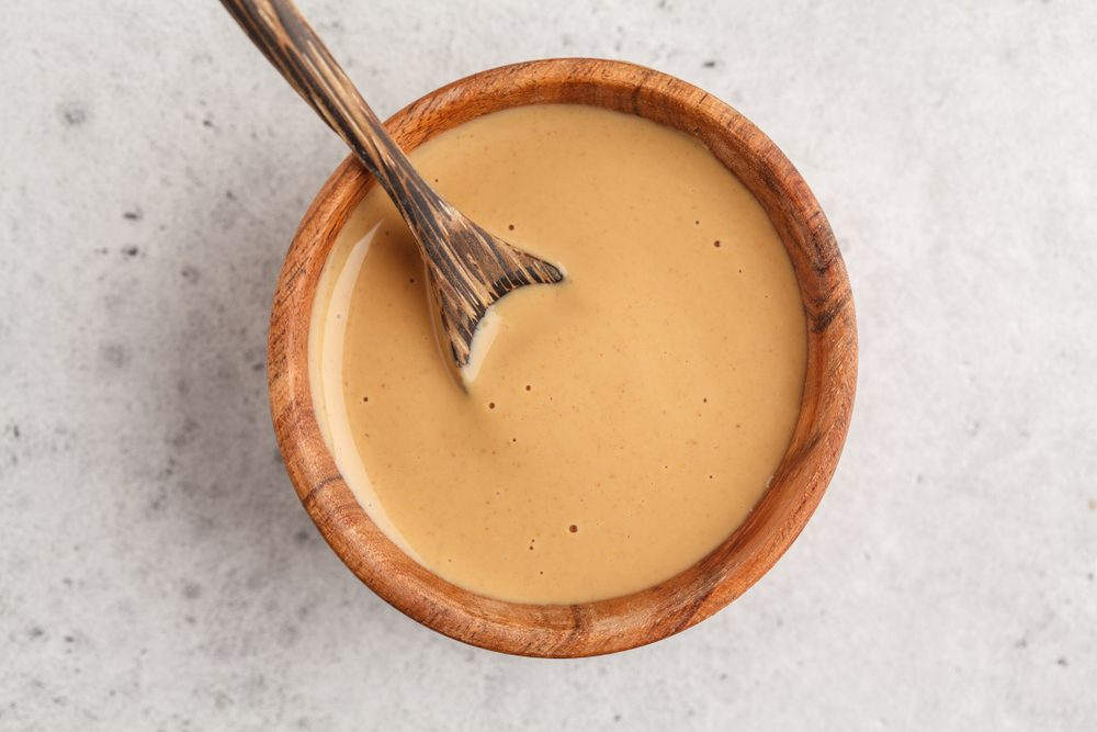 Creamy homemade peanut butter in a wooden bowl, top view. Healthy vegan food concept.