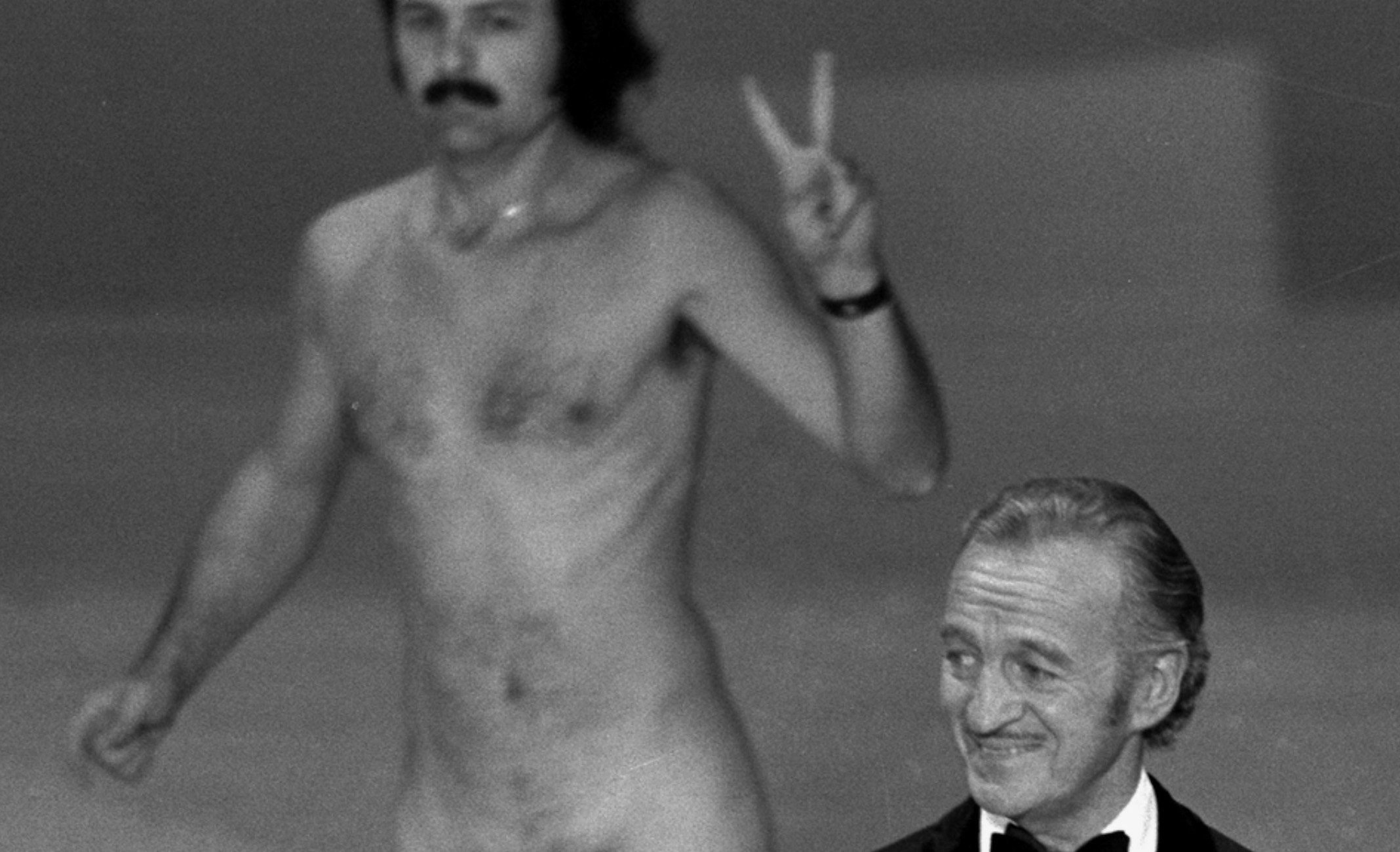 Mandatory Credit: Photo by Anonymous/AP/Shutterstock (6594477a) Actor David Niven presents an award as streaker Robert Ope crosses the stage during the 1974 Academy Awards show in Los Angeles Film Five Most, LOS ANGELES, USA