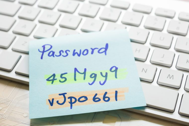 "Handwriting passwords with ""nhighlight colors written on blue paper note on top of modern white keyboard with wooden office table on background. Login access, data privacy and cyber security concepts."