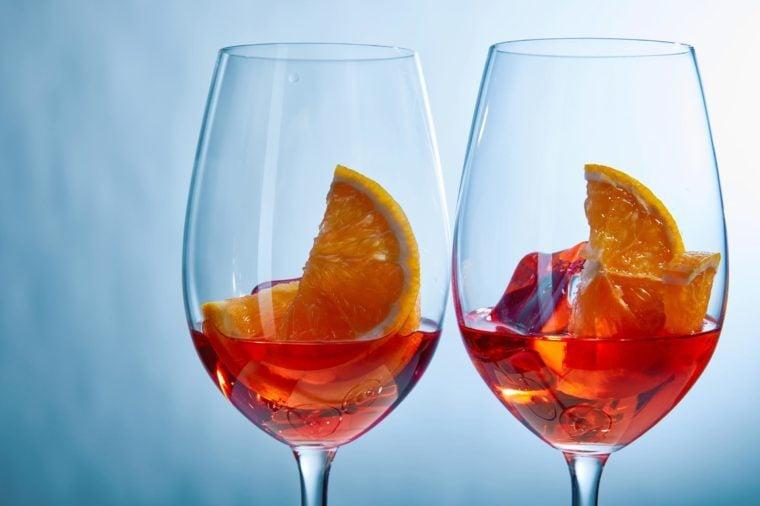 two wine glasses, apertol spritzes, on blue background