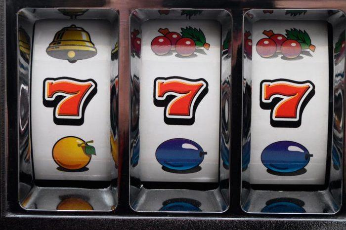 close up of slot machine with winning sevens