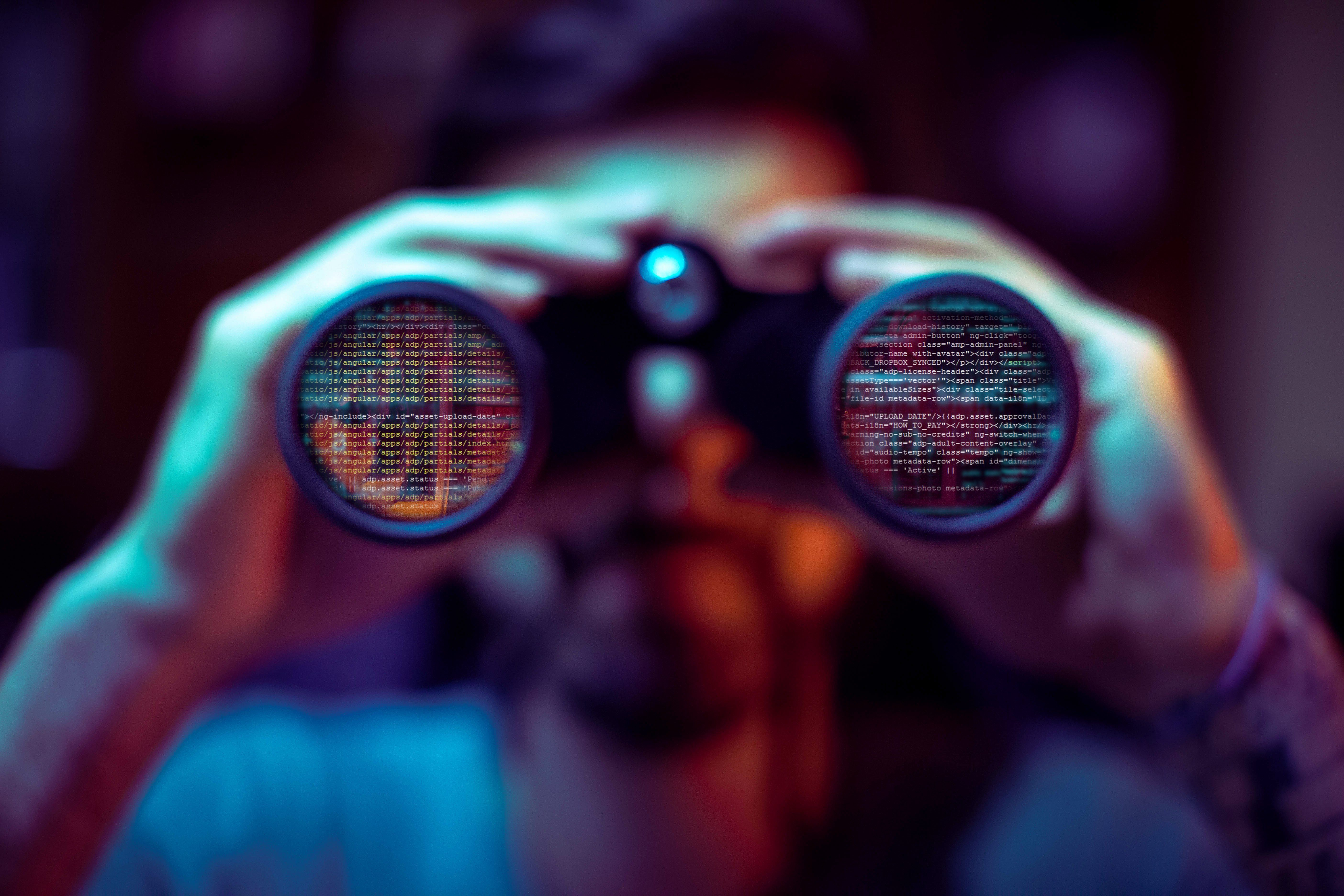 man with binoculars. the binoculars reflect computer code.