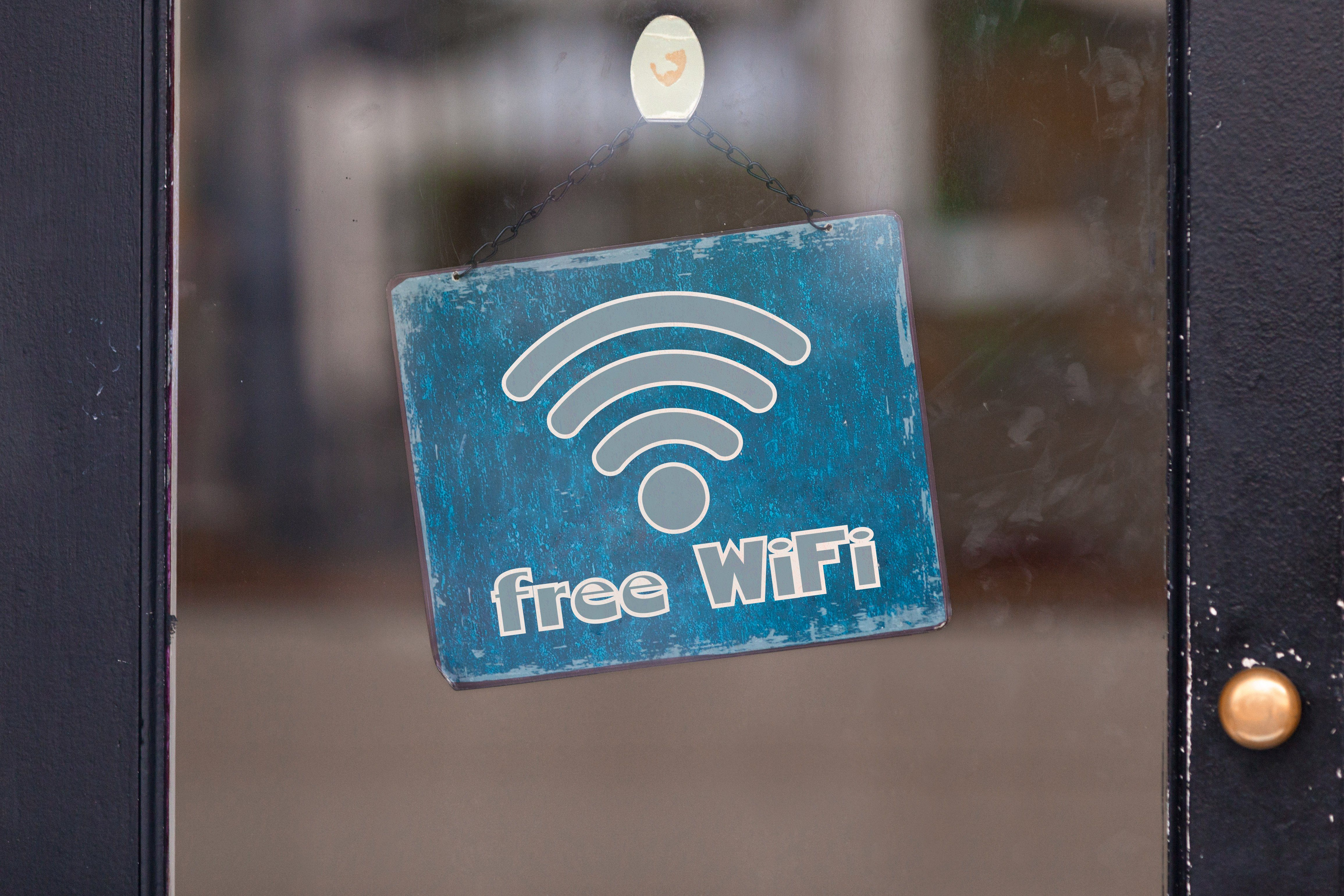 "Sign attached to a glass door saying ""Free WiFi""."
