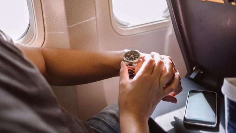 man looking at his watch in an airplane