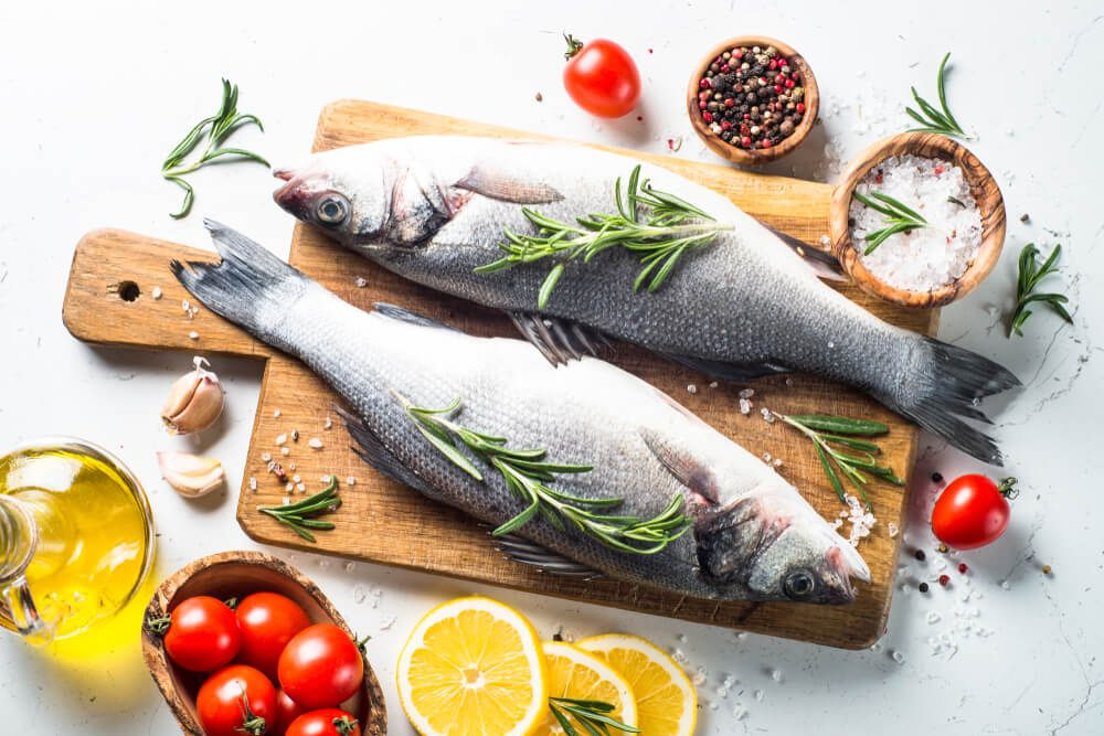 Fresh fish seabass. Raw fish seabass with spices and herbs ingredients for cooking on white background. Top view.