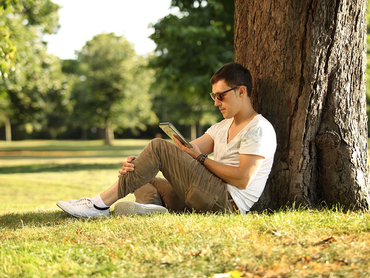 Benefits of being alone - man using tablet in park