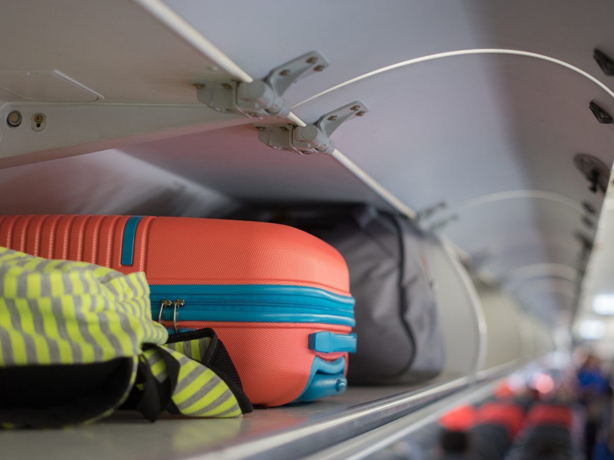 Carry-on luggage on the top shelf over head on airplane