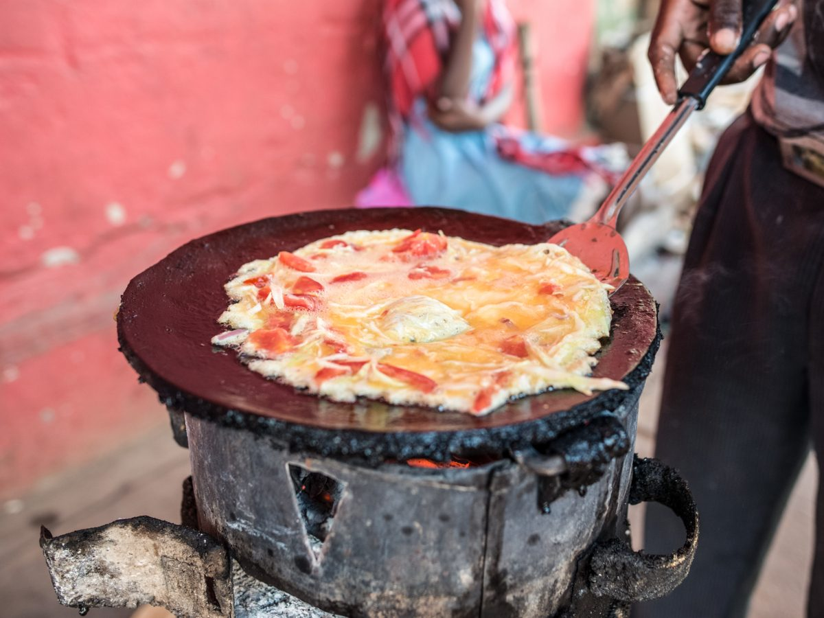 "Ugandan man cooking ""Rolex,"" a local dish"