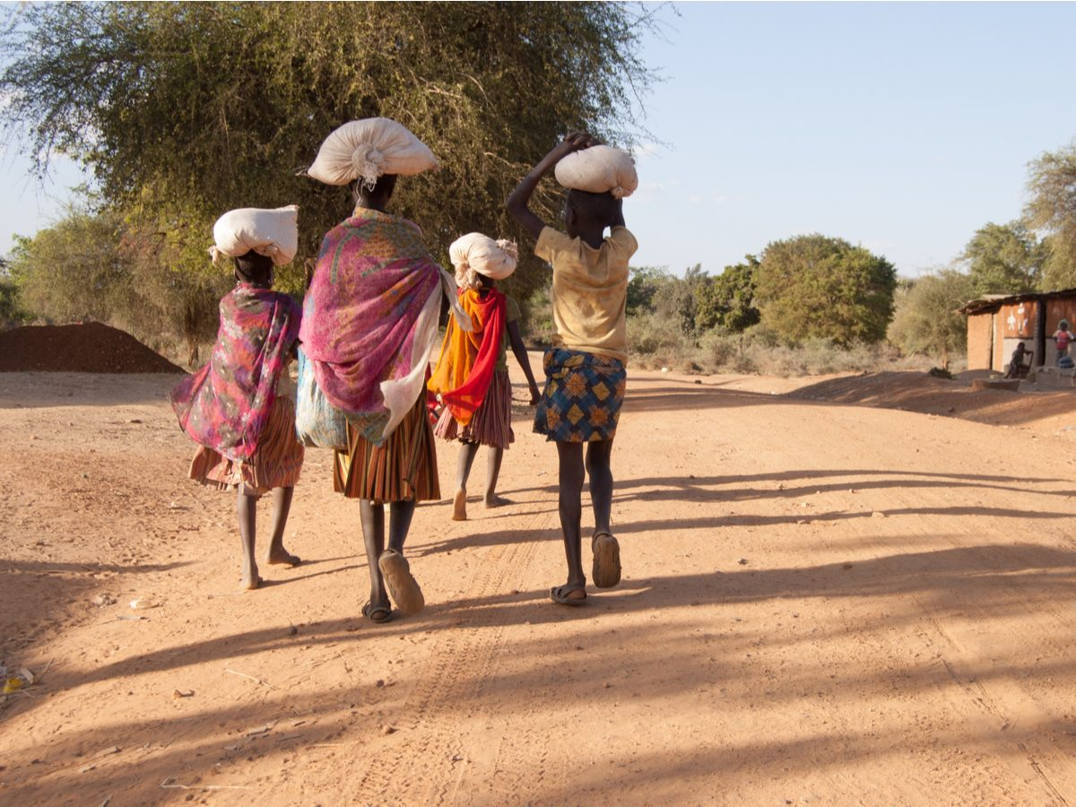 Group of African girls carrying bags of food in Uganda, East Africa