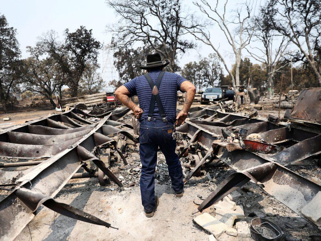 Man walking through rubble of home