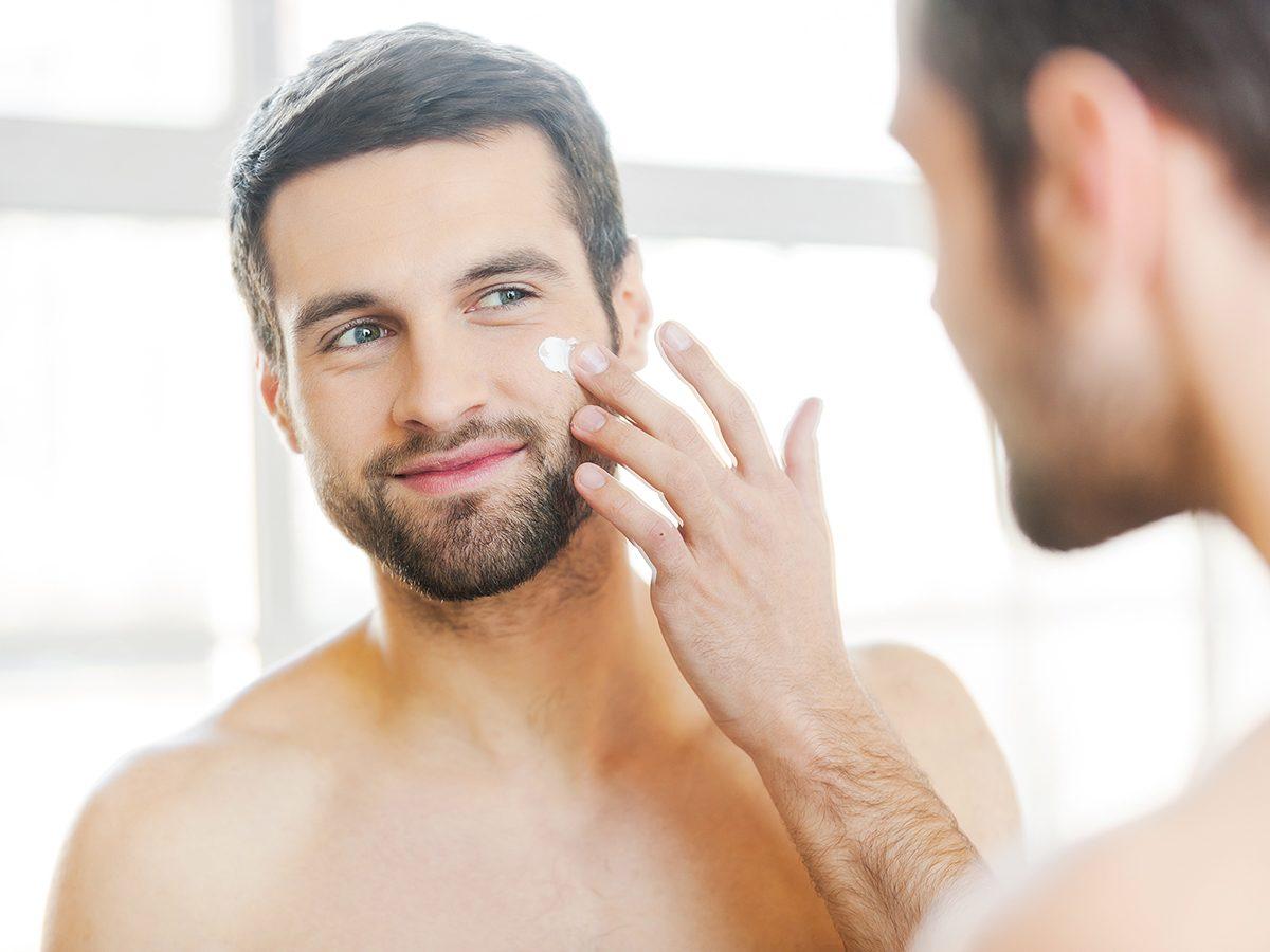 Glowing skin secrets - man applying moisturizer