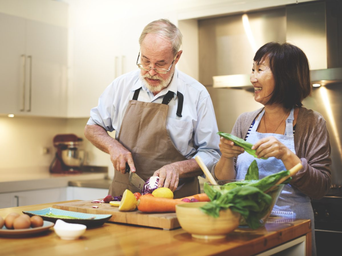 Happy senior couple cooking healthy meal in kitchen