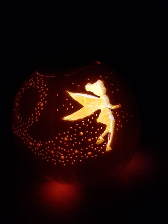 Pumpkin with Tinkerbell carved on the front and a candle inside