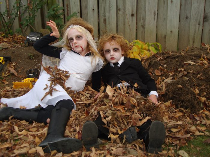 Two kids in zombie costumes in a pile of leaves