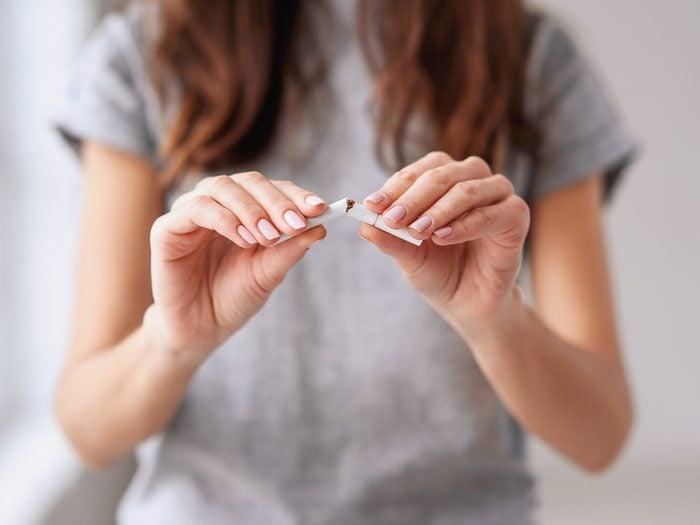 Person breaking a cigarette in half