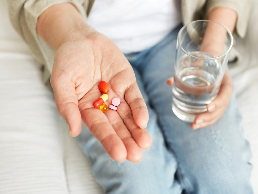 Person holding pills and glass of water