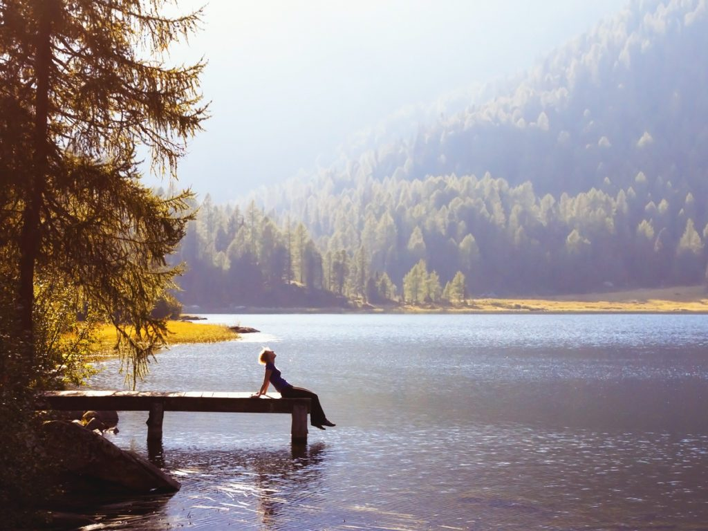 Woman seen from a distance sitting on a dock by a lake