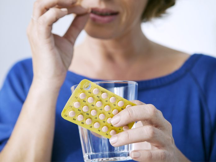 Woman taking an HRT pill
