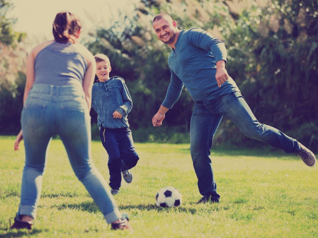 Family of three playing soccer